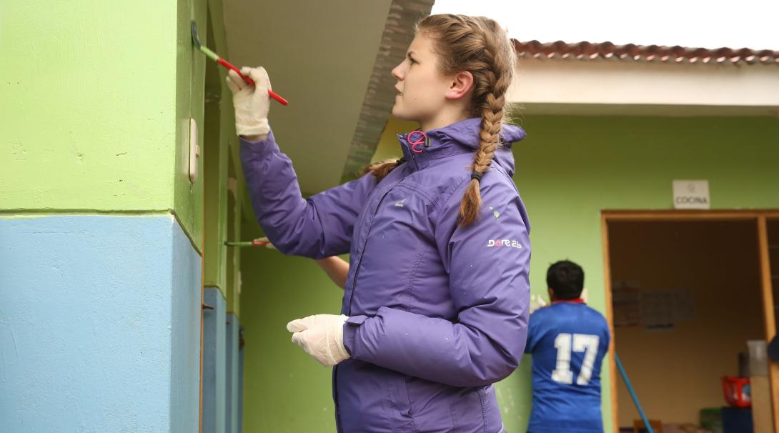 As part of her community volunteer work in Peru, a teenager volunteer paints a wall of a local primary school.